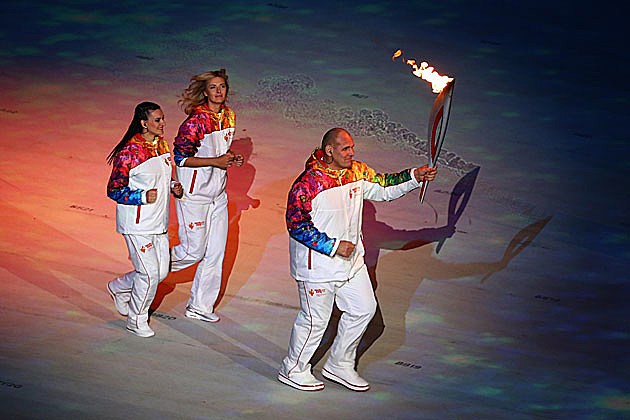 Alexandr Karelin carries the Olympic torch, alongside Elena Isinbaeva and Maria Sharapova